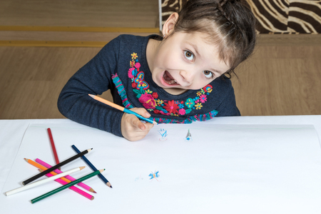 Little girl draws pencil on a large white paper emotional mouth open