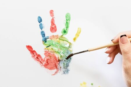 handprint: Female hand with a brush paints a colorful handprint on a white sheet