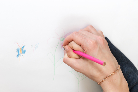 kid drawing: Mom teaches her child to draw holding his hand in her close-up