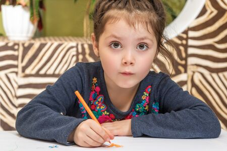 eyes wide open: Little beautiful girl draws pencil sitting at the table and looking at the camera with eyes wide open Stock Photo