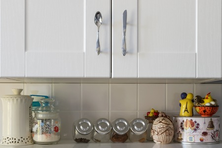White kitchen shelf with spices and cupboard on top closeup Banco de Imagens