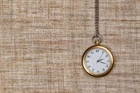 arabic numerals: Antique analog clock with Arabic numerals on a chain on the background of burlap Stock Photo