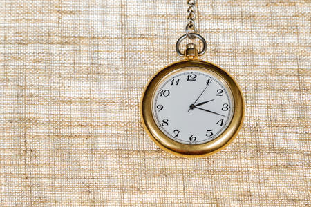 arabic numerals: Antique analog mechanical clock with Arabic numerals on a chain on the background of burlap Stock Photo