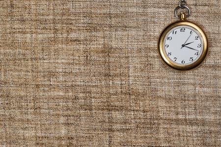 corner clock: Pocket analog gold clock in the corner against a background of burlap