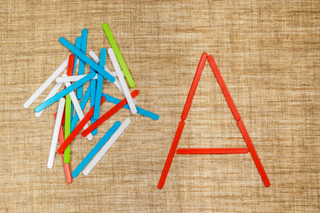 alphabet letter a: Game to assemble the letters from children colored sticks on cloth sacking