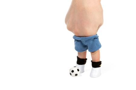 depict: Fingers dressed in shorts, leggings and boots depict footballer with ball isolated on white background Stock Photo