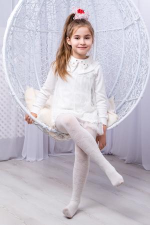 Ritratto di una bella bambina seduta su altalena - cellulare in studio