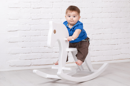 surprised baby: Little surprised baby sitting on a white horse, wooden rocking Stock Photo