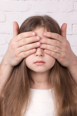 beautiful eye: Portrait of serious child girl with strange hands closing her eyes