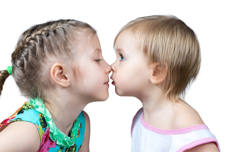 rubbing noses: Two children look at each other and touched noses isolated on white background