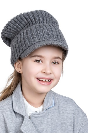 one girl: Portrait of a cheerful little girl in a gray knitted cap isolated on white background