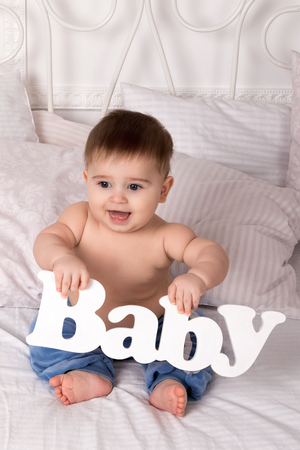cute babies: Portrait of a small child sitting on a bed and holding a lettering in her hand -baby Stock Photo