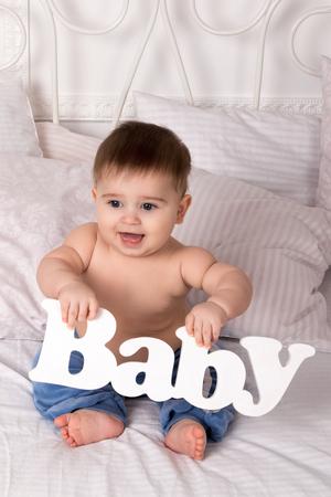 bebes lindos: Retrato de un niño pequeño sentado en una cama y sosteniendo un letrero en la mano -baby