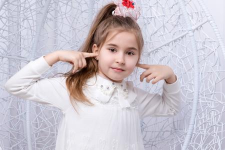petite fille avec robe: Belle petite fille dans une robe blanche couvrait son index leurs oreilles
