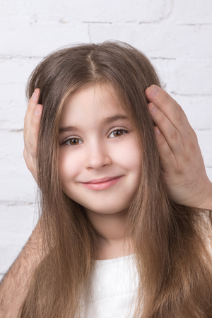 cute teen girl: Closeup portrait a smiling a child girl whose adult man covered her ears