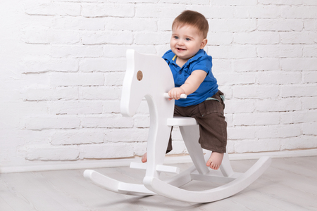 Little smiling baby sitting on a white horse, wooden rocking