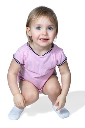 squatting down: Little girl with blue eyes crouched down isolated on white background