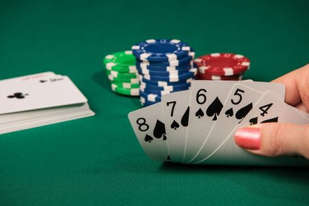 consecutive: A female hand lifts the cards from the poker table with a combination of five consecutive peak