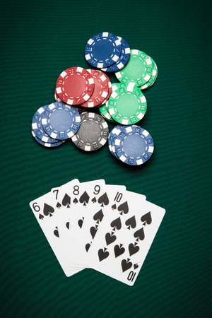 straight flush: Poker hand of five cards of Straight Flush on a green table next to chips