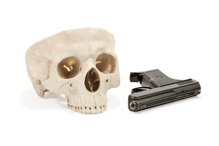 eye socket: Human skull and a small black metal gun lying near isolated on white background