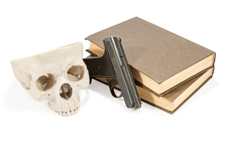 eye socket: Two brown books lying one on another, next gun and a human skull isolated on white background