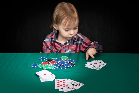 straight flush: Child playing a poker points his finger at a winning combination of a straight flush