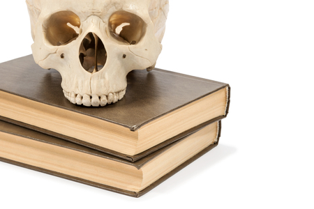 eye socket: Human skull lying on a stack of two books isolated on white background