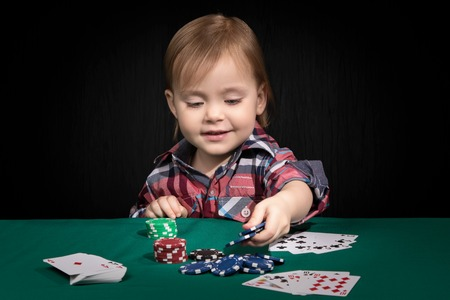 bets: Child bets playing poker with open cards and benefits from a combination of