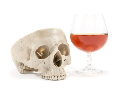 addictive drinking: Human skull and a glass half filled with alcoholic beverage isolated on white background