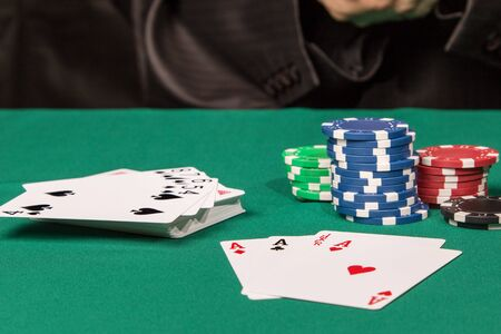 straight flush: Deck of cards with a straight flush at the top next to the aces and poker chips on a green table