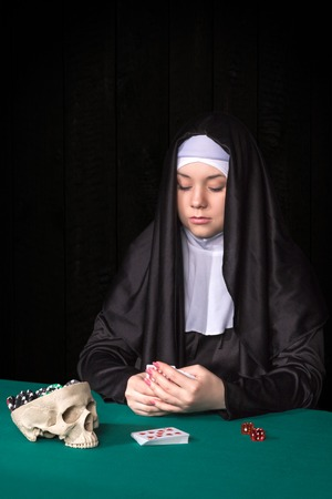 black nun: Nun playing cards at green poker table hands covering his cards isolated on a black background
