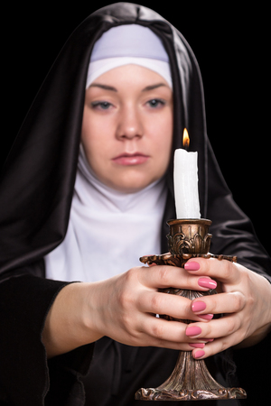 black nun: Nun holds a burning candle in his outstretched hands. Candle clearly nun blurry. Isolated on black background