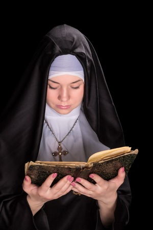 black nun: Nun is reading an old worn bible isolated on a black background