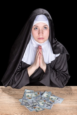 black nun: Nun sitting at a wooden table, praying for money isolated on a black background Stock Photo