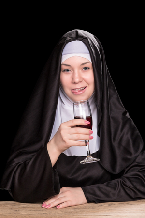 black nun: Nun tongue out while sitting at a wooden table with a glass of wine in hand, isolated on a black background Stock Photo