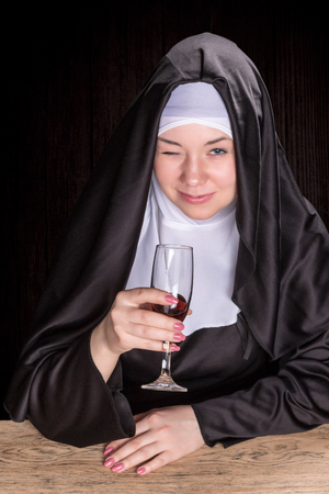 religious habit: Nun sitting at a wooden table and holding wine in a glass cup and winking with one eye Stock Photo