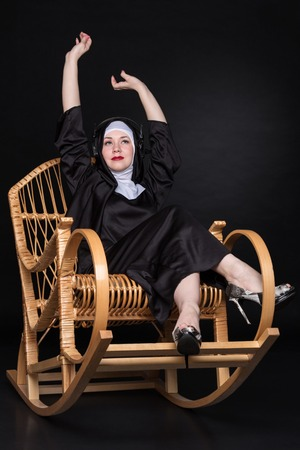 rocking chair: Funny nun wearing headphones and waving his hands to the music while sitting in a rocking chair