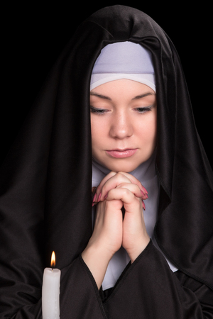 black nun: Portrait of a young nun praying with burning candle isolated on black background Stock Photo