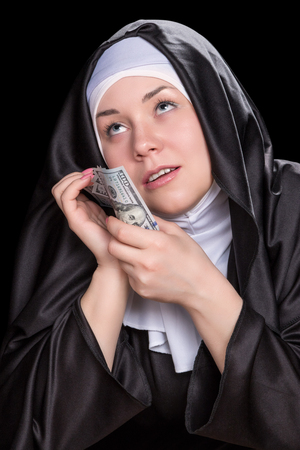 black nun: Joyous nun pressed her face to the money and looking up isolated on a black background Stock Photo