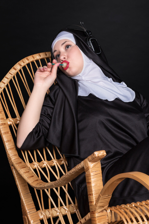rocking chair: Nun sitting in a rocking chair sucking candy and listening to music on headphones Stock Photo