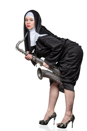 temptative: Portrait of a nun with bright makeup holding a saxophone between legs isolated on white background