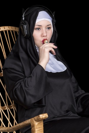 rocking chair: Nun sitting in a rocking chair sucking candy and listening to music on headphones close-up