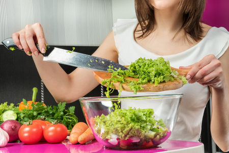 adding: Female hands adding lettuce leaves into bowl with salad, close-up