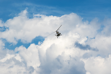 awry: Military helicopter is flying at the camera in the blue sky with clouds