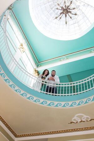 second floor: Portrait of a bride and groom standing next to railing on the second floor bottom view