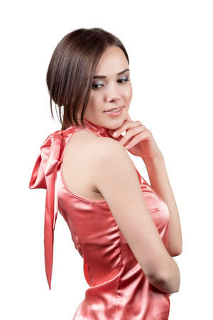 Portrait of a beautiful young woman in a red satin dress isolated on white background