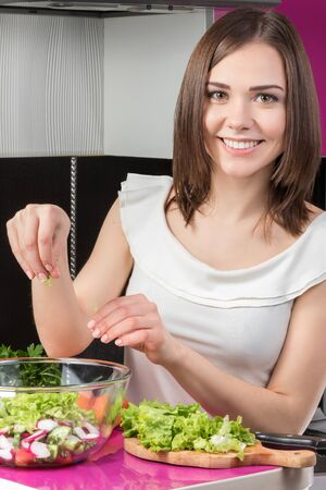 adds: Portrait of a young smiling woman that adds in a bowl of salad lettuce Stock Photo