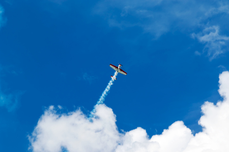 manoeuvre: Red and white sport plane flies up releasing a stream of smoke into the blue sky with clouds