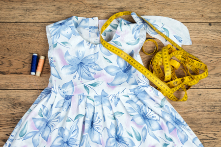 cotton dress: Still life of thread, tape measures and elements cotton dress lying on the old vintage wooden table