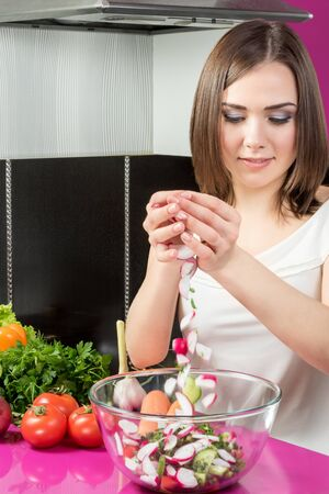 adds: Young beautiful woman adds sliced radishes in a bowl with a salad standing at a table in the kitchen